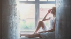Depressed Young Woman Sitting on Window Edge 1 with sunrays Stock Footage