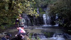 Tourist taking selfies and photos at Purakaunui Falls, located in the Catlins, N Stock Footage