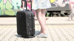 Person with suitcase on wheels at train station closeup4K Stock Footage
