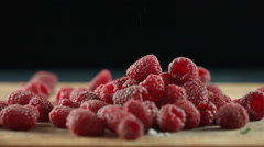 Sugar powder falling on the heap of red raspberries on the surface Stock Footage