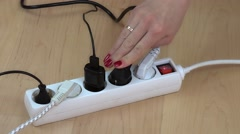 Female hands connect wire plugs to extension switch on wooden floor Stock Footage