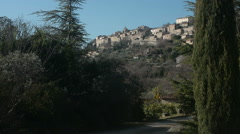General view of Gordes seen from afar amid trees, Provence, France Stock Footage