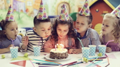 Children blowing out candles on birthday cake Stock Footage