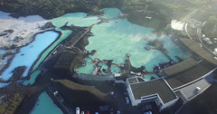 Aerial circling around the Blue Lagoon in Iceland as steam rises from the water Stock Footage