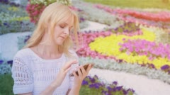 Happy smiling girl using a smart phone in a city park sitting on a bench 6 Stock Footage