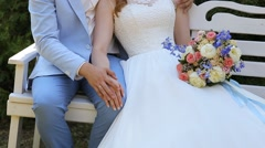 The couple sitting on the white bench, holding hands Stock Footage