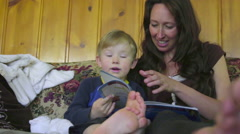 Mom reads book to kid Stock Footage