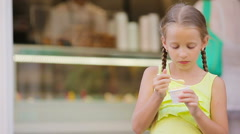 Adorable little girl eating ice-cream outdoors at summer. Cute kid enjoying real Stock Footage