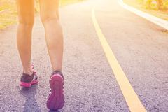 Closeup of feet for woman runner athlete  running on the road or street Stock Photos