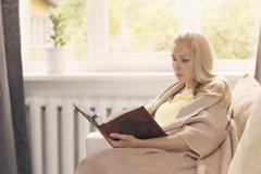 Woman resting on the couch and read a book Stock Photos