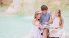 Family with touristic map near Fontana di Trevi, Rome, Italy. Happy father and Stock Footage