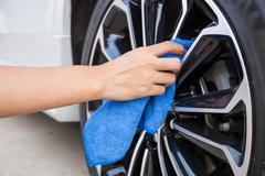 Hand with blue microfiber cloth cleaning car wheel. Kuvituskuvat