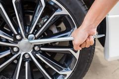 Hands disassembling a modern car wheel (steel rim) with a lug wrench Stock Photos