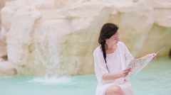 Beautiful woman looking at touristic citymap near Trevi Fountain, Rome, Italy Stock Footage