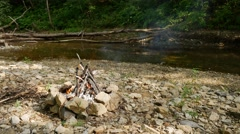 Campfire by the river in a deep wood UHD Stock Footage