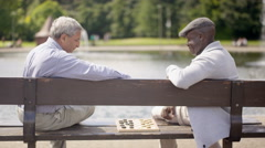 4K Happy senior male friends playing draughts in the park Stock Footage