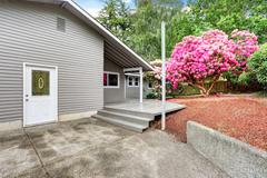 Well kept backyard garden of siding trim house with wooden walkout deck. Nort Stock Photos
