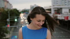 Wind blows long dark hair beautiful young women. happy, smiling girl standing on Stock Footage