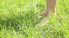 Woman's bare feet walking over green grass field, she throwing shoes on grass Stock Footage