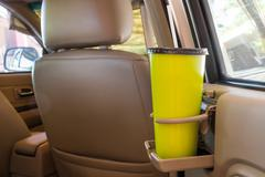 Coffee or tea mugs green placed on the vehicle console in modern luxury car i Stock Photos