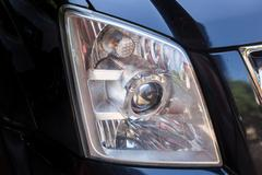 Closeup headlights of modern black car with projector lens Stock Photos