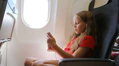 Adorable little girl traveling by an airplane. Kid listening music sitting near Stock Footage