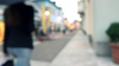Blurred slim brunette girl with umbrella walking with her purchasings in paper Stock Footage