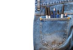Pencil and magic pen in a pocket blue jeans on white isolated background. Stock Photos