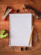 Top view from blank notepad workspace with pencil, glasses, paperclip Stock Photos