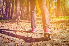 Woman nordic walking outdoors feet close up Stock Photos