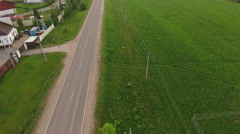 Car driving on asphalt country road through the green meadow and townhouse villa Stock Footage