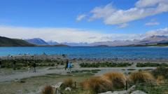 New Zealand Lake Tekapo with tourists walking along Stock Footage