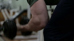 Bodibilder shakes her biceps with dumbbells in the gym Stock Footage