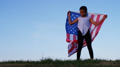 Young child drapes herself in a US flag standing at sunset, in slow motion Stock Footage