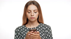 Upset young beautiful blonde girl looking at phone over white background Stock Footage