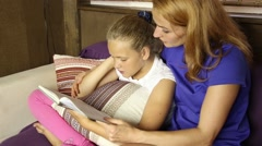 Young mom reading a book aloud to her daughter in the living room on the couch Stock Footage
