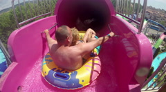Couple having fun going down the extreme water slide closed tube Stock Footage