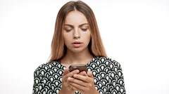 Upset young beautiful blonde girl looking at phone over white background. Slow Stock Footage