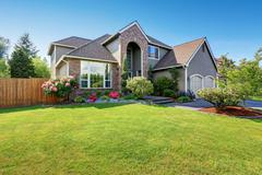 Luxury house exterior with brick and siding trim and double garage. Well kept Stock Photos