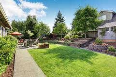 Well kept garden at backyard with concrete floor patio area and opened red um Stock Photos