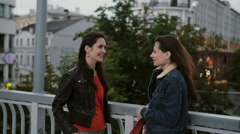 Two beautiful girls best friends standing on the city bridge, talking, smiling Stock Footage