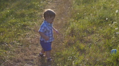 The one year old cute fair-head boy is making his first steps Stock Footage