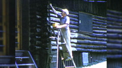 Man on Ladder Paints House Log Cabin 1960s Vintage Film Home Movie 9911 Stock Footage