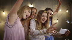Young beautiful cheerful girls making selfie, smiling, resting at party. Slow Stock Footage