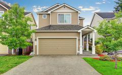 American house exterior with garage, driveway and well kept lawn. Northwest,  Stock Photos