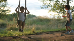 Two children, boy brothers, having fun on a swing in the backyard on sunset Stock Footage