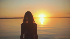 Happy young woman walking with arms stretched out standing on a beach Stock Footage