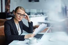 Tense female holding business documents over laptop Stock Photos