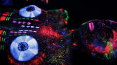 Hands DJ govern painted fluorescent powder on the body of a naked girl decks Stock Footage