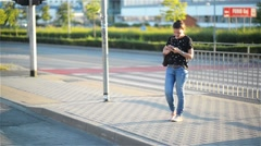 Young woman texting with a smartphone in urban background, beautiful girl using Stock Footage